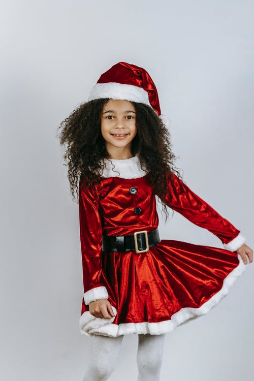 Positive African American girl with curly hair wearing Santa Claus dress and Santa hat looking at camera while standing on white background