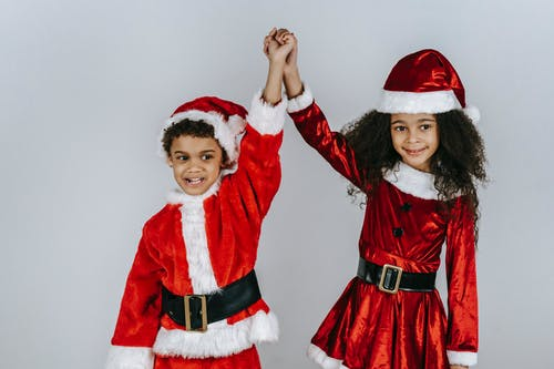 Charming African American children in colorful Santa costumes looking away with raised arms during Christmas holiday on light background