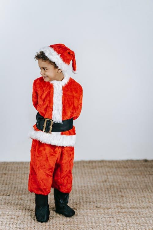 Black boy in Santa costume on Christmas day