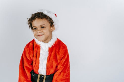 Smiling black boy in Santa costume on light background