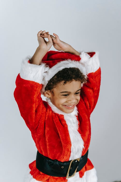 Smiling ethnic kid in bright Santa costume looking down with raised arms on Christmas day on light background