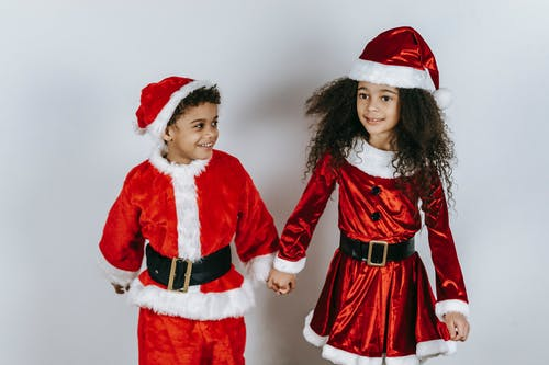 Smiling ethnic siblings in Santa costumes celebrating New Year holiday