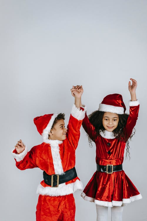 Charming African American siblings in bright Santa costumes holding hands while having fun during New Year holiday on light background