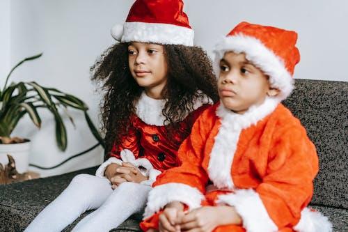 Black siblings in Santa costumes resting on sofa at home