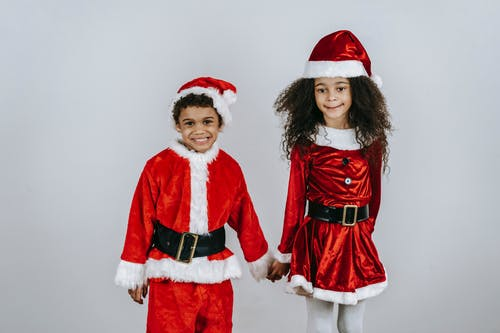 Sincere black sister with brother in bright Santa costumes celebrating New Year holiday on light background