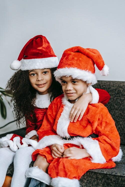 Black girl embracing brother on couch during New Year holiday