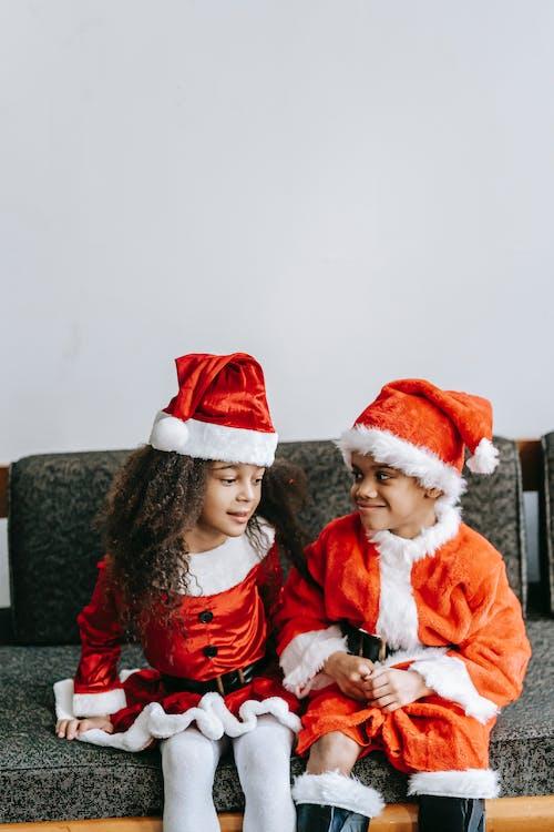 Charming black siblings in Santa costumes interacting on sofa indoors