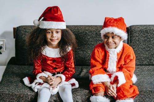 Content black children in Santa costumes resting on sofa