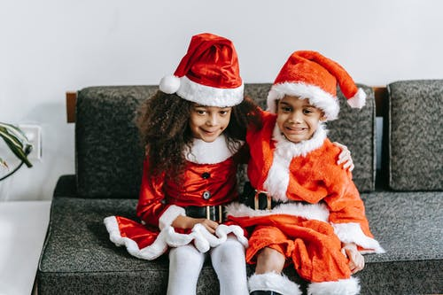 Glad ethnic sister embracing brother in Santa costume while celebrating Christmas holiday on sofa and looking away at home