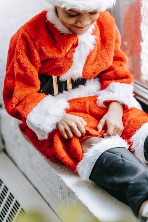 Crop smiling black boy in Santa costume on windowsill