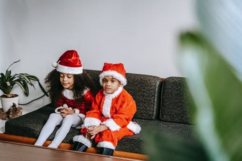 African American girl with clasped hands sitting on couch near brother in bright Santa costume during New Year holiday at home