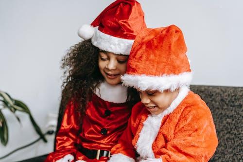 Adorable black children in Santa costumes sitting on sofa