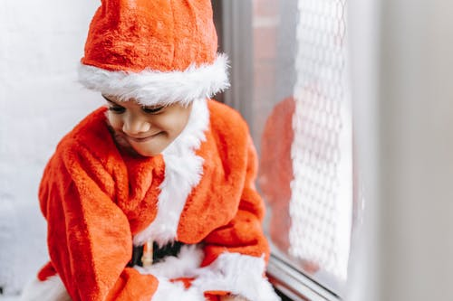 Adorable content African American boy wearing red Santa costume and hat sitting on windowsill and looking down