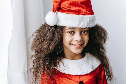 Smiling black girl in Santa costume standing near window