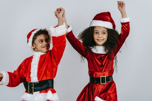 Carefree African American siblings wearing red Santa costumes and hats holding hands and jumping happily against white wall in studio