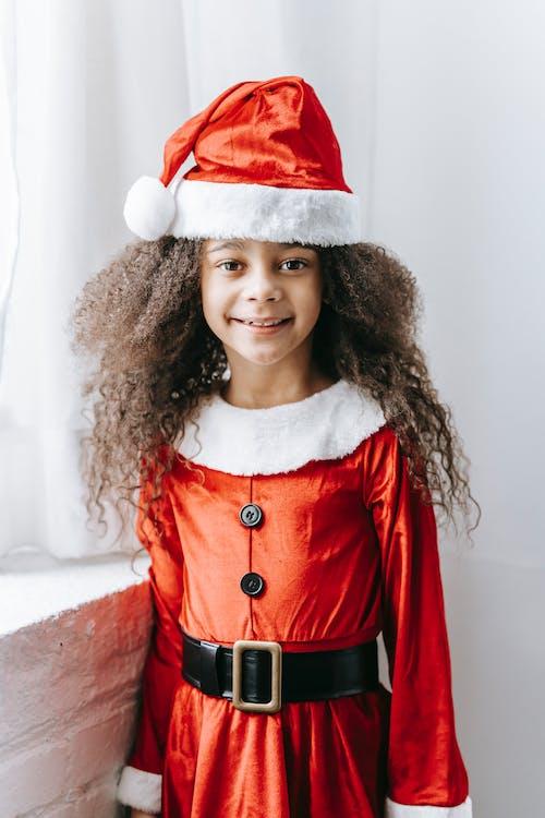 Cheerful black girl in Santa clothes standing near window