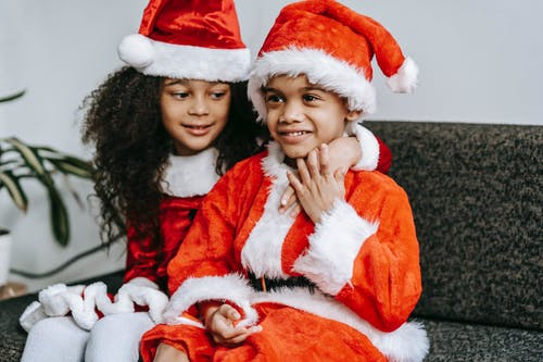 Smiling black kids in Santa costumes hugging on soft couch