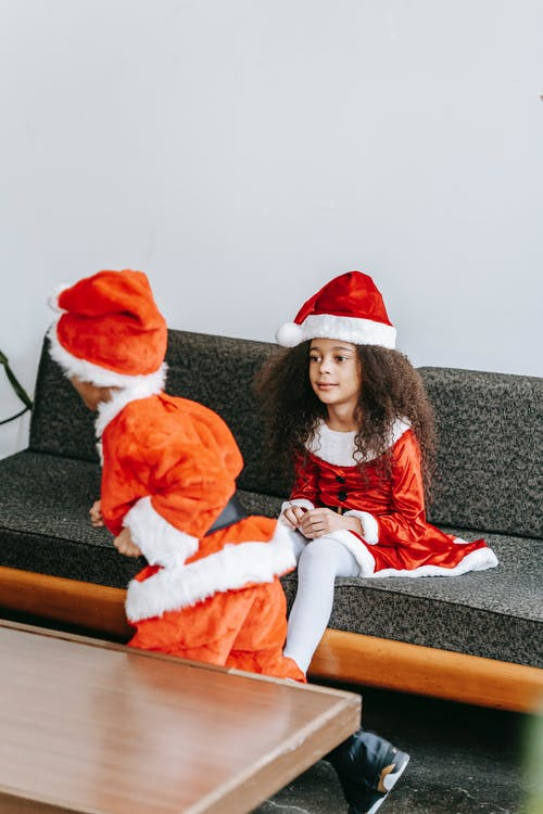 Content African American children wearing red Santa Claus costumes playing together on cozy couch during festive season