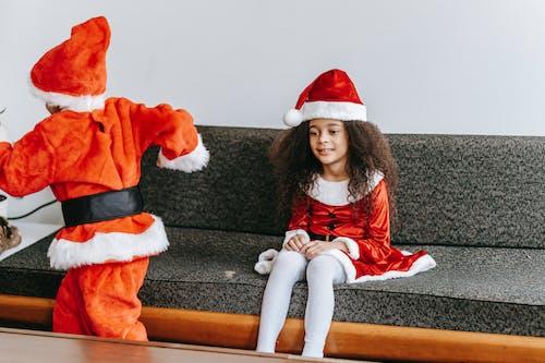Cute black siblings in Santa costume playing near sofa