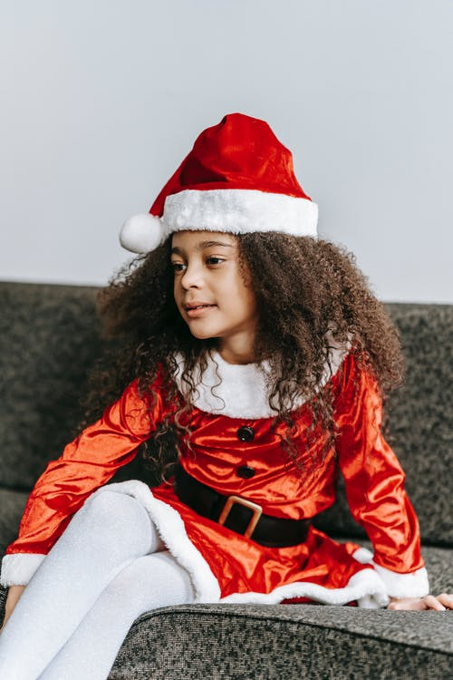 Content African American girl wearing Santa Claus dress and hat sitting on comfy couch and looking away during festive holidays
