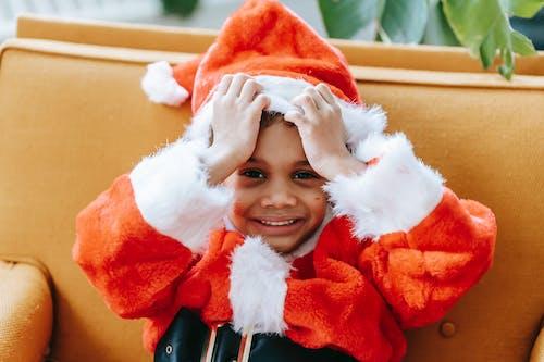 Happy black boy in Santa costume sitting on cozy armchair