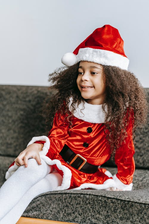 Smiling black girl in Santa clothes resting on couch