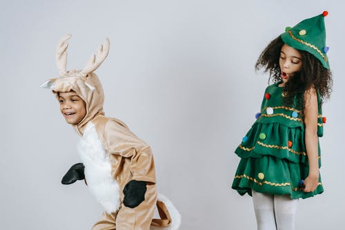 Cheerful African American siblings in Christmas tree and deer costumes playing and having fun together in light studio