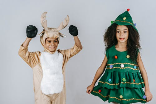 Cheerful black kids in Christmas costumes playing in studio
