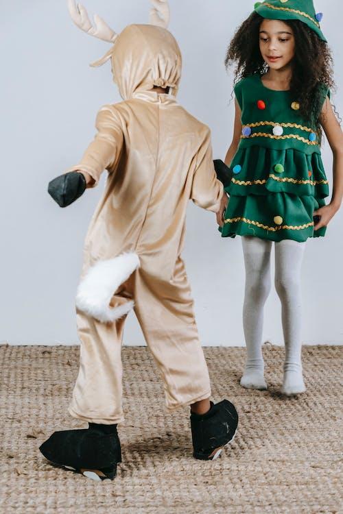 Cute black kids in Christmas costumes dancing in studio