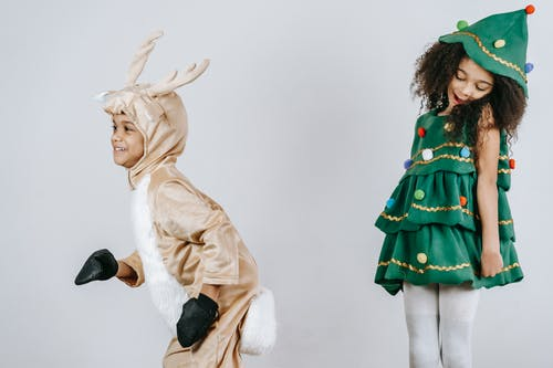Adorable happy African American children wearing creative festive costumes playing and having fun together in light studio