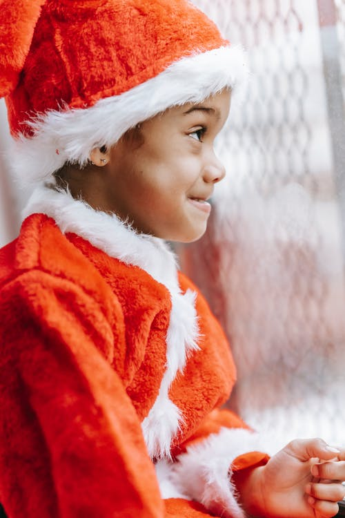 Funny black boy in Santa costume standing near window