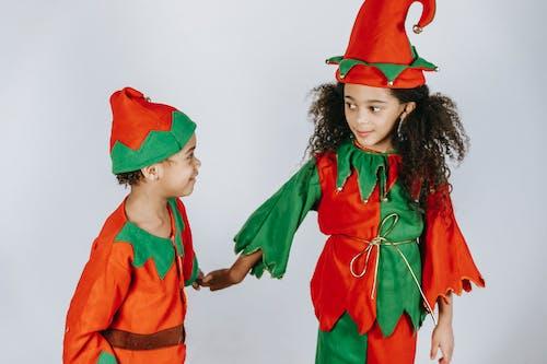 Positive black siblings in elf costumes holding hands