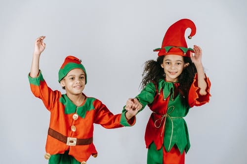 Optimistic African American siblings wearing colorful elf outfits with hats holding hands while standing on white background during Christmas holiday