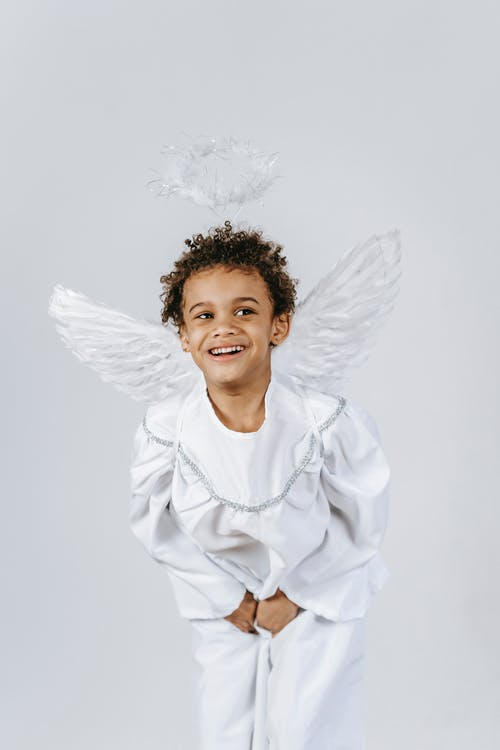 Cute African American boy with curly hair wearing white angel outfit with halo and wings looking away while standing on white background during holiday