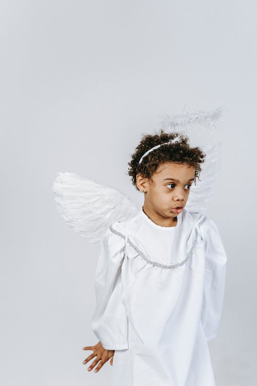 Adorable black boy in angel outfit during holiday celebration
