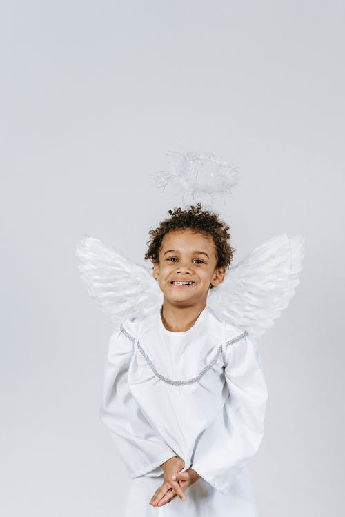 Optimistic African American boy wearing white angel costume with wings and halo smiling and looking away while standing on white background during Christmas celebration