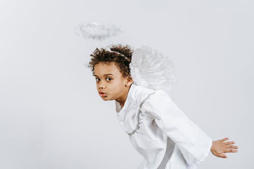 Cheerful black boy in angel costume during festive event