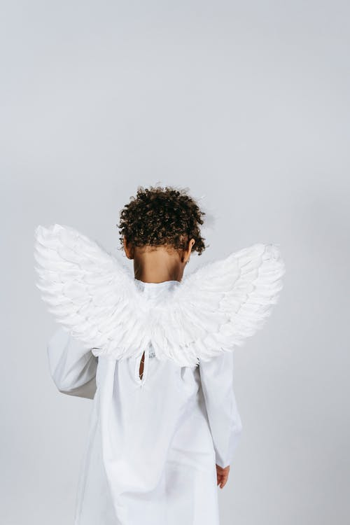 Back view of unrecognizable African American boy wearing white angel outfit with wings standing on white background during Christmas holiday