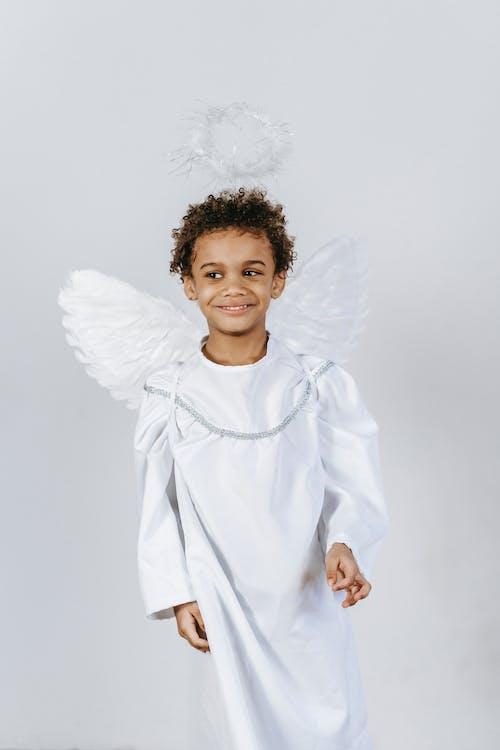 Cute black boy in costume of angel