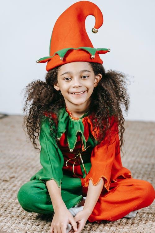 Cute glad black girl in costume of elf