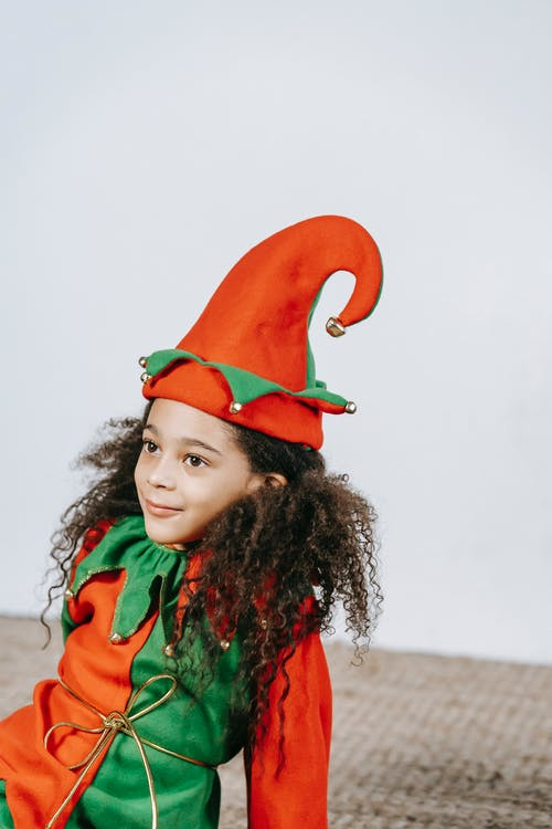 Cheerful adorable African American girl with curly hair in bright red and green costume of elf