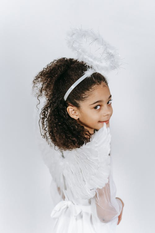 Adorable little African American girl in costume of angel with gentle wings smiling and looking at camera on white background