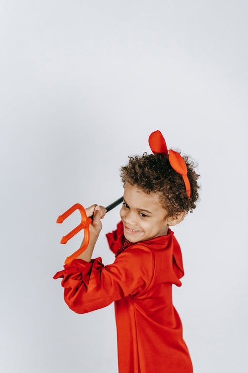 Cheerful African American boy with curly hair in bright red costume of devil smiling and looking away on white background