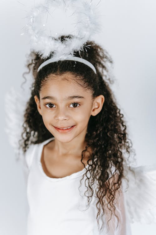 Cute black girl in costume of angel with soft nimbus
