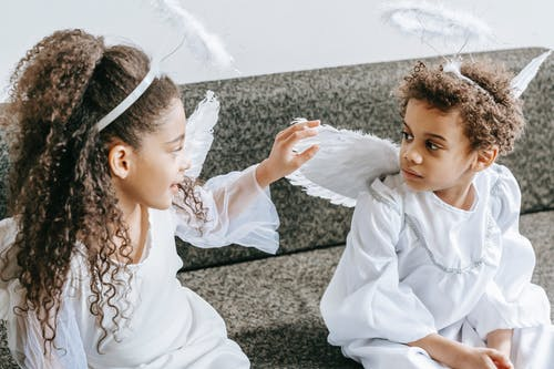 Little cute African American girl with curly hair touching wing of angel costume of friend