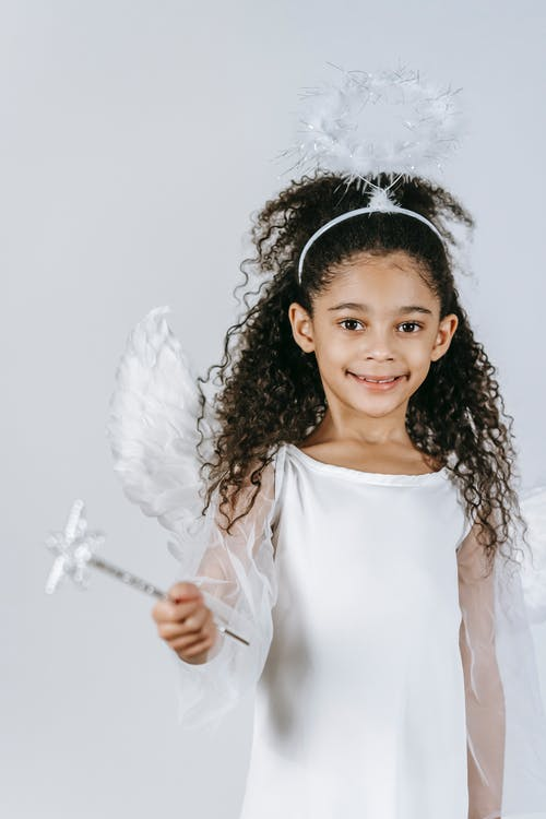 Adorable little African American girl in costume of angel smiling and looking at camera on white background