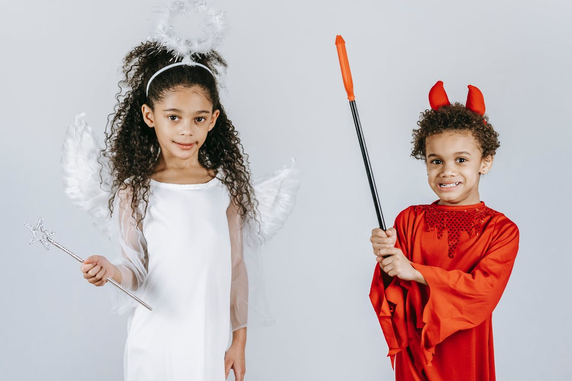 Black children in costumes of angel and devil