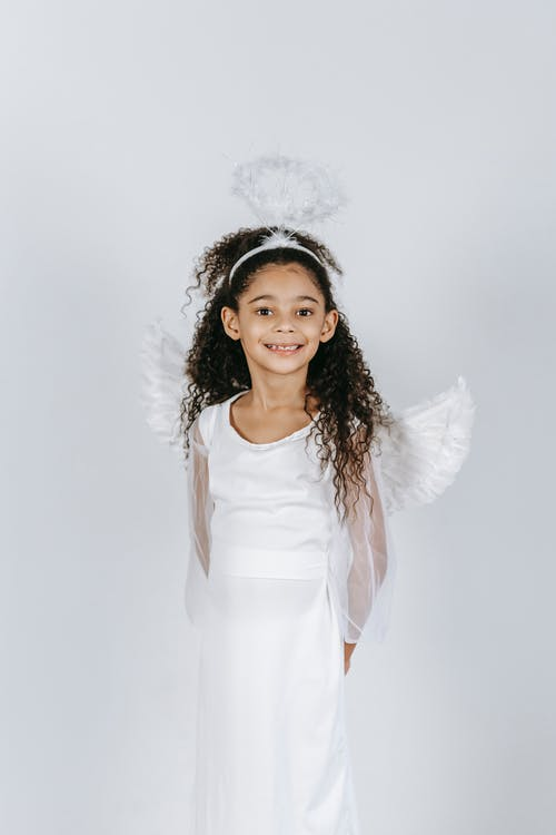 Adorable little African American girl with long curly hair in white costume of angel smiling and looking at camera in studio