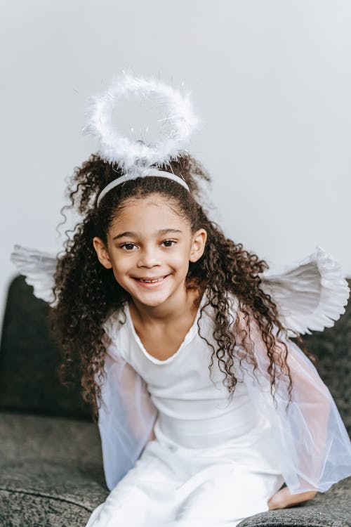 Delighted adorable black little girl with long curly hair in white costume of angel with wings and halo sitting on comfortable sofa and looking at camera