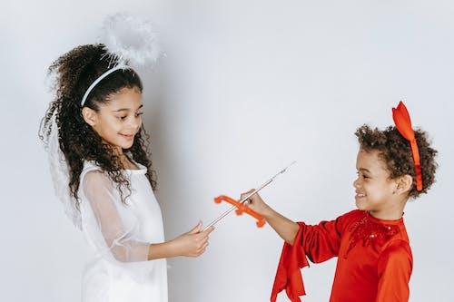 Positive black kids pretending to be angel and devil in studio